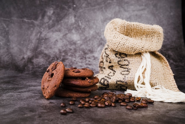 Baked cookies and roasted coffee beans with sack on rustic backdrop