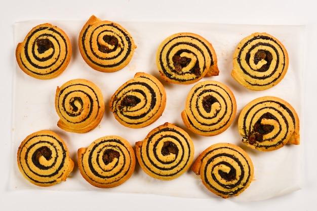 흰색 배경에 분리된 건포도와 양귀비 씨가 있는 구운 쿠키.