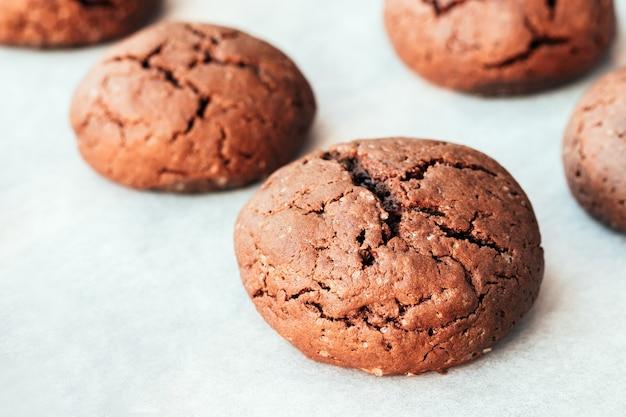 Запеченное круглое шоколадное печенье с трещинами на противне с пергаментной бумагой, только что вынутым из духовки. чайная закуска. выборочный фокус. крупным планом вид