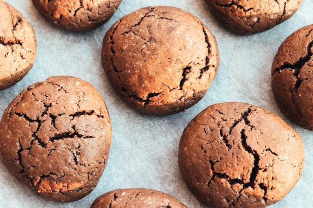 Запеченное круглое шоколадное печенье с трещинами на противне с пергаментной бумагой