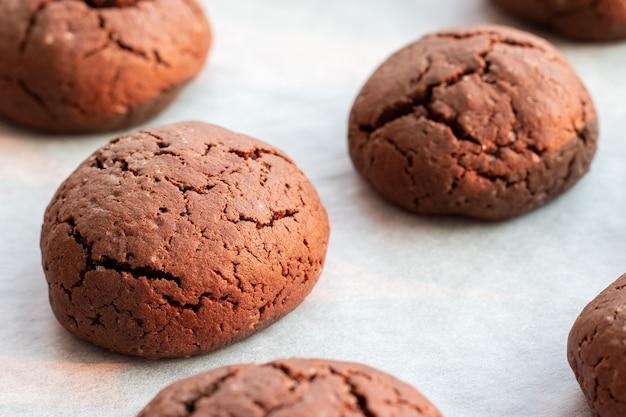 Запеченное треснувшее круглое шоколадное печенье на противне с пергаментной бумагой