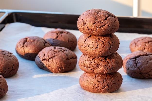 Запеченное круглое шоколадное печенье с трещинами, сложенное на противне с пергаментной бумагой
