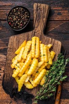 구운된 크링클 감자 튀김 감자 스틱 또는 나무 보드에 칩. 어두운 나무 배경입니다. 평면도.