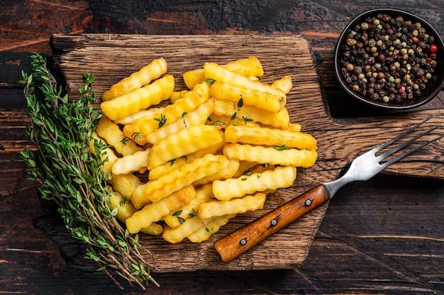 Запеченные картофельные палочки или чипсы crinkle french fries на деревянной доске