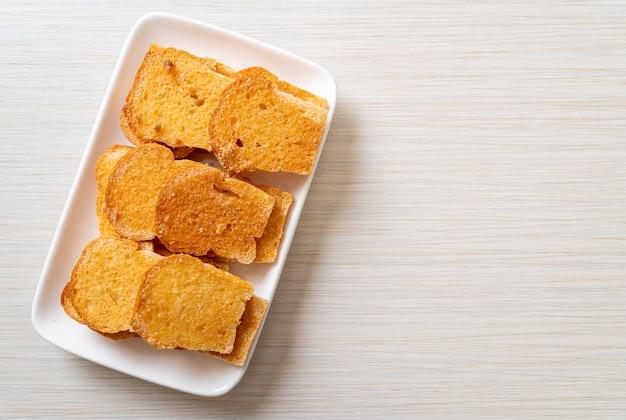 Испеченный хрустящий хлеб с маслом и сахаром на тарелке