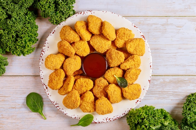 Baked crispy chicken nuggets with ketchup on white plate.
