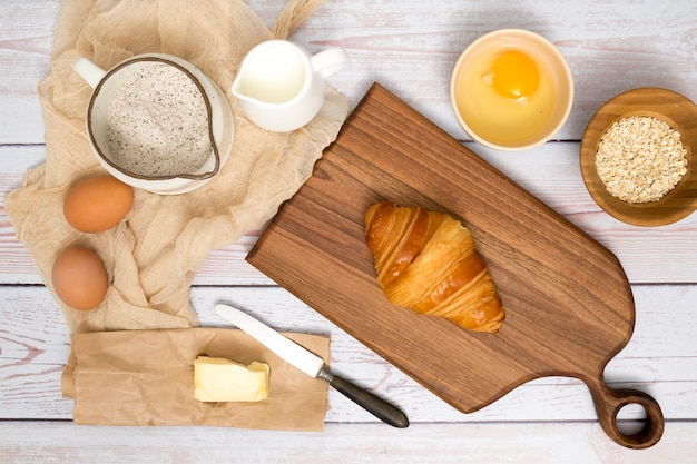 Baked croissant on chopping board with ingredients on wooden plank