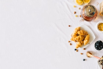 Baked croissant; fruits; tea and dryfruits on white background