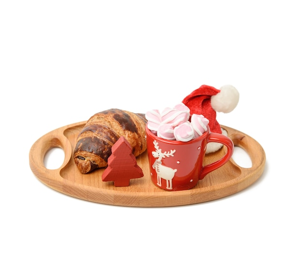 Baked croissant and red ceramic cup with cocoa and marshmallows, white surface