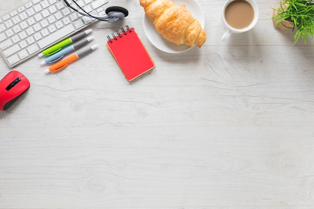 Baked croissant and tea cup with keyboard and office supplies on wooden table with space for writing text