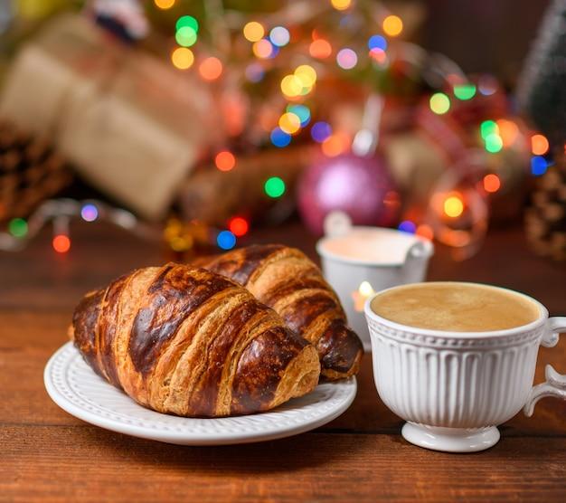 Запеченные круассаны и белая керамическая чашка с кофе за горящими рождественскими огнями