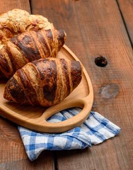 Запеченные круассаны лежат на деревянном подносе, еда на коричневой поверхности, вид сверху