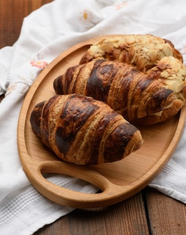 Baked croissants lie on a wooden tray, food on a brown background, top view