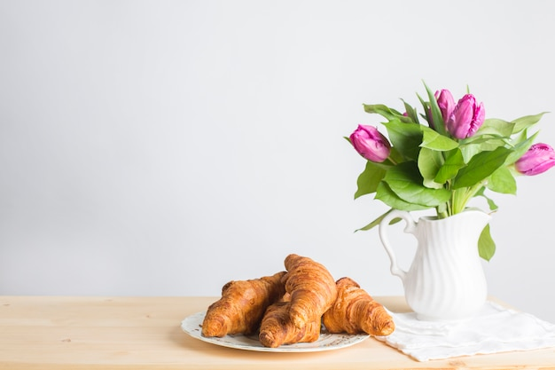 Baked croissants plate near the vase on wooden desk isolated on white background