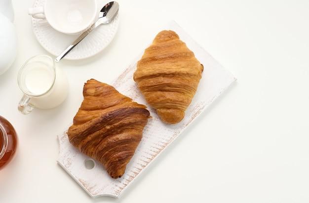 구운 크루아상, 흰색 세라믹 찻주전자, 빈 컵과 접시, 흰색 탁자에 있는 꿀 항아리, 위쪽 전망. 아침밥