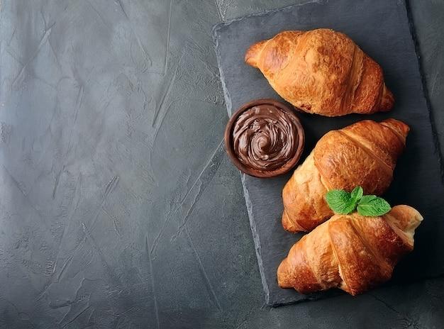 Запеченные круассаны с шоколадной пастой на черном столе. вид сверху завтрак