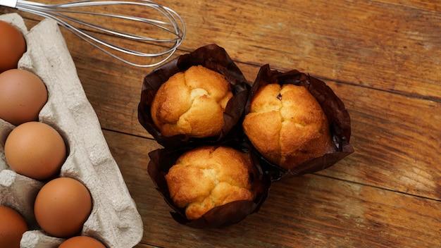 소박한 나무 배경에 구운 컵케이크와 머핀. 쟁반에 담긴 계란, 반죽 거품기, 맛있는 신선한 머핀