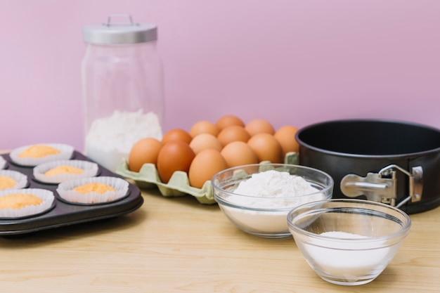 Baked cupcakes; eggs; flour; sugar; baking tin on wooden table