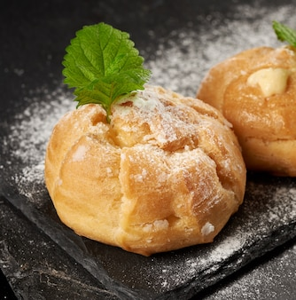 Baked custard eclairs and sprinkled with powdered sugar and decorated with a mint leaf