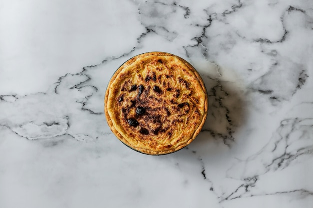 Baked custard tart on marble background, top view
