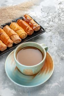 Запеченные восхитительные браслеты внутри черной формы с молочным кофе на сером, выпечка печенье, торт сладкое