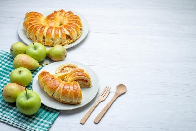 Запеченный восхитительный браслет из теста, сформированный внутри стеклянной тарелки вместе с яблоками и грушами на белом столе, печенье, бисквит, сладкое печенье