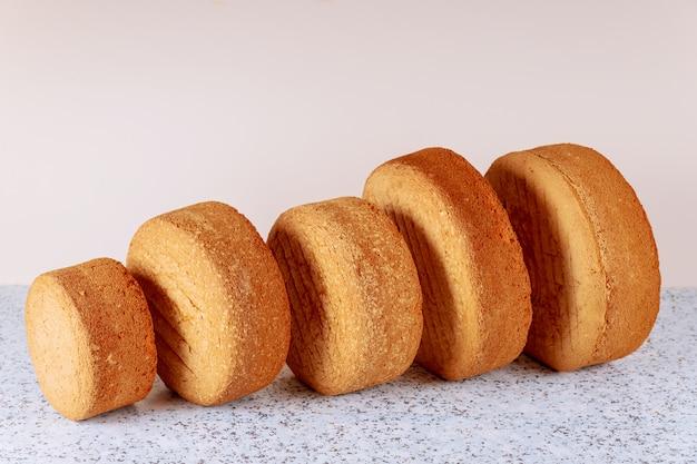 Запеченные бисквиты разных размеров на столе для изготовления свадебного торта