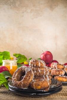 Запеченные пончики с сахаром, глазурью с корицей и белым сахаром сверху, на деревянном фоне со свежими яблоками