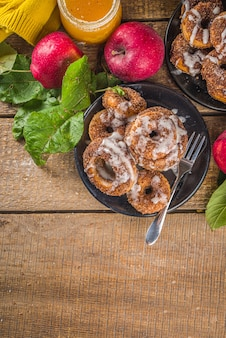 Baked donuts with sugar, cinnamon glaze and white sugar topping drizzle, on wooden background with fresh apples