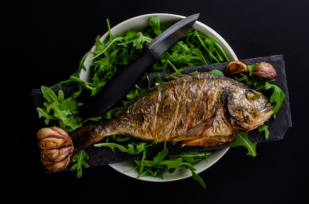 Baked dorada fish garnished with arugula in a bowl and knife on black background