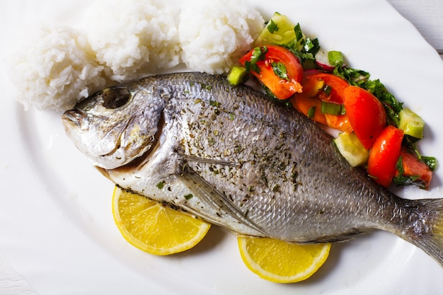 Baked dorado fish with rice and salad on the white plate