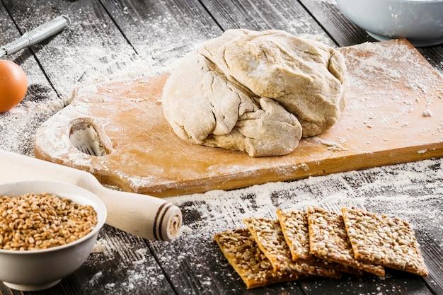 Запеченное тесто на разделочной доске и здоровое печенье с семенами подсолнечника и семенами льна