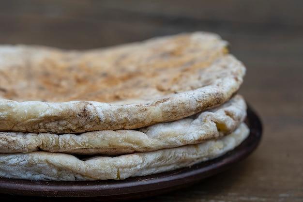 Запеченная лепешка из теста с творогом и зеленью в керамической тарелке на деревянном столе, крупным планом, традиционное турецкое блюдо