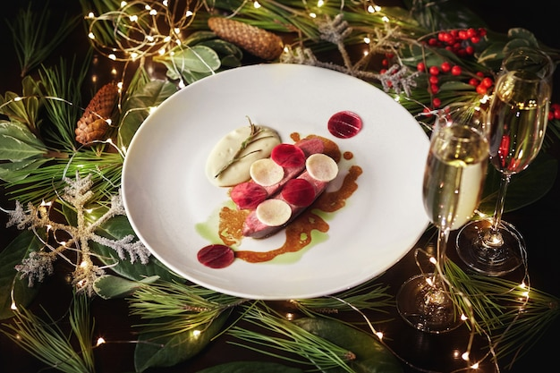 クリスマスの装飾が施されたテーブルの上に大根とホワイトソースを添えた焼き鴨胸肉