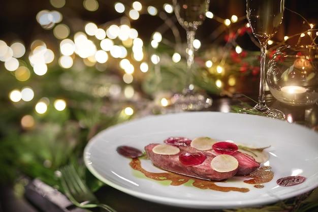 お祝いのクリスマステーブルに大根とベシャメルソースを添えた鴨胸肉の焼き物