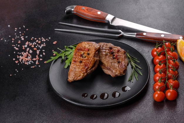Baked duck breast with herbs and spices on a dark concrete surface. fried meat ready to eat