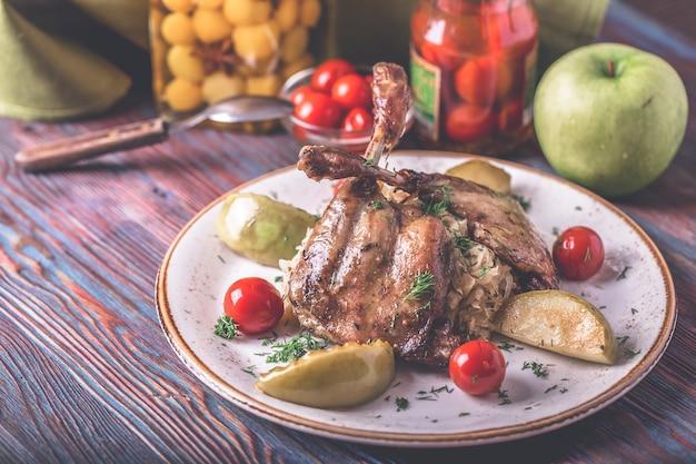 Baked duck legs  garnish. tasty roasted duck legs  sauerkraut and tomatoes.