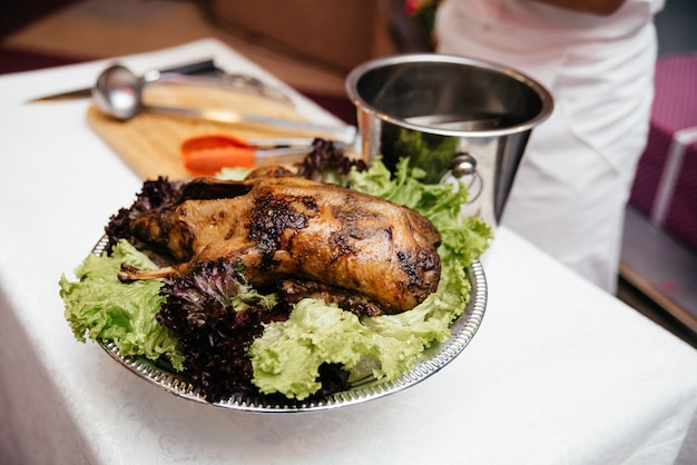 Baked duck on a platter with vegetables and salad