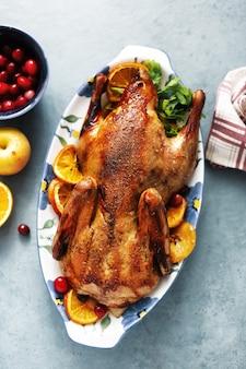 Запеченная утка с овощами подается на столе. вид сверху.