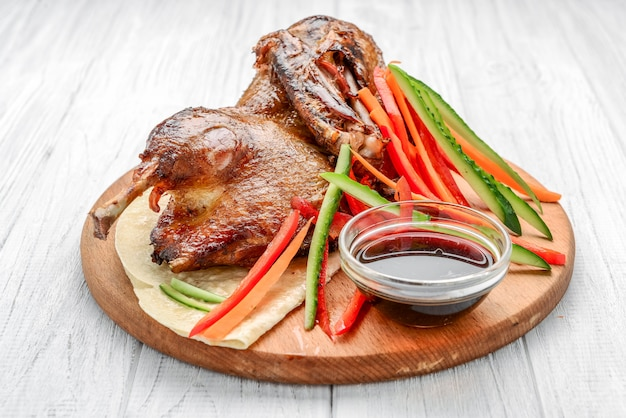 Baked duck with vegetables on a wooden surface