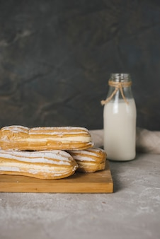 Baked eclairs on wooden chopping board with milk bottle