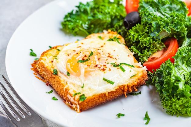 白いプレートにサラダと焼き卵とチーズのトースト、クローズアップ。
