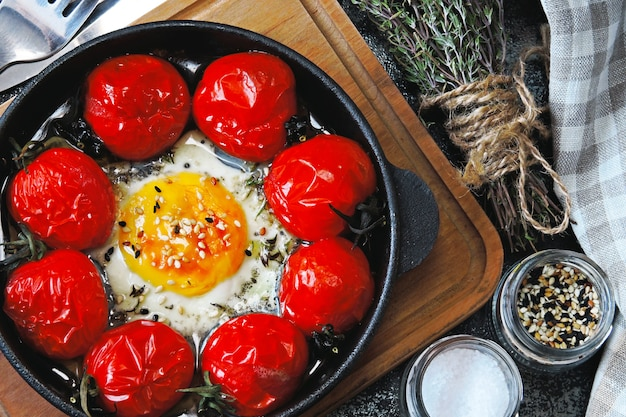 Baked egg with cherry tomatoes in a cast iron skillet