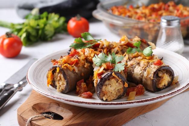구운 된 가지 롤 나무 보드에 접시에 닭고기, 양파와 당근. 확대. 수평 형식.