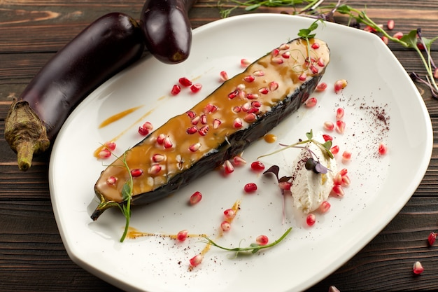 Запеченный баклажан с семенами сыра и граната, на белой тарелке, на деревянном столе