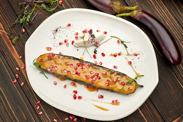 Baked eggplant with cheese and pomegranate seeds, on a white plate, on wooden table