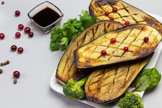 パセリとブロッコリーを添えた焼きナス。ボウルにソース、テーブルにクランベリー。灰色の背景。上面図