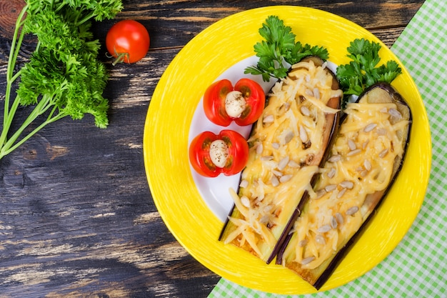 Baked eggplants with parmesan, sunflower seeds and tomatoes.