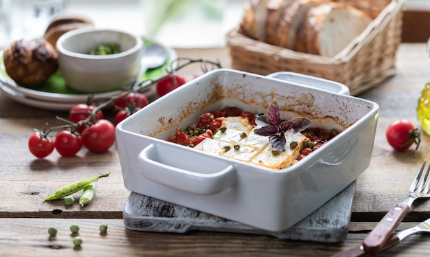 Baked feta cheese with cherry tomatoes with basil and olive oil. greek national cuisine.