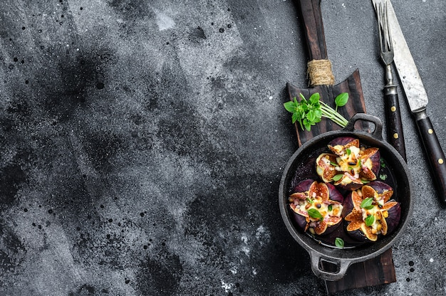 Запеченный инжир с козьим сыром, вермутом, медом и грецкими орехами. черный фон